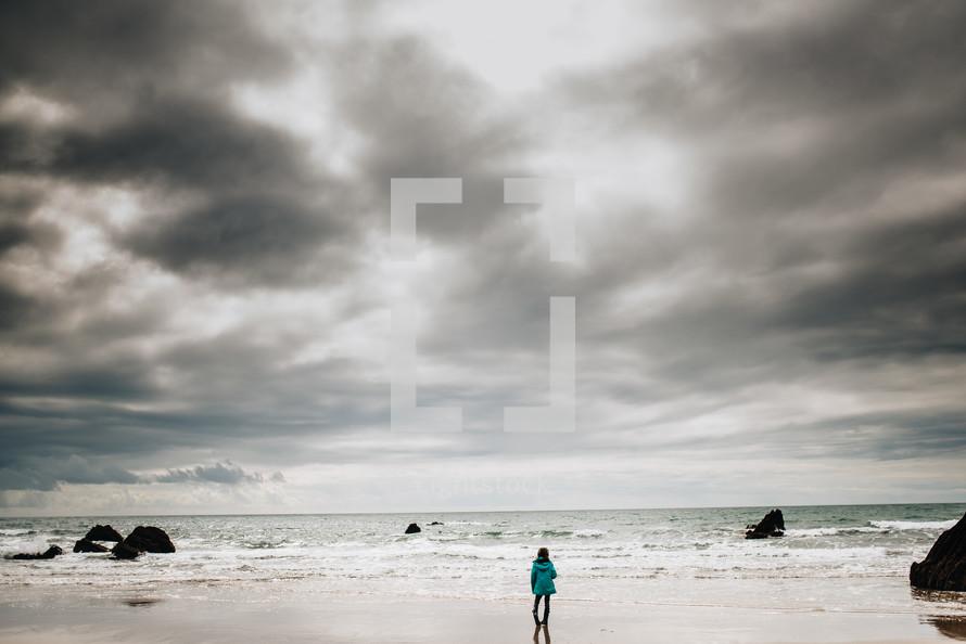 a girl standing on a beach