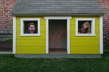 Man and woman peeking out windows of miniature yellow house.