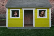 Man and woman peeking out windows of miniature yellow house.