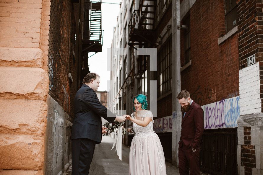 bride and groom standing in an alley