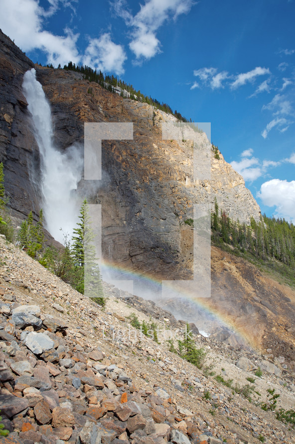 waterfall with rainbow - mountain cliff