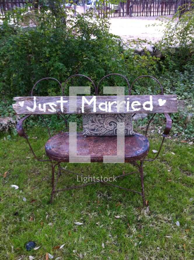 """Just Married"" wood sign on chair"