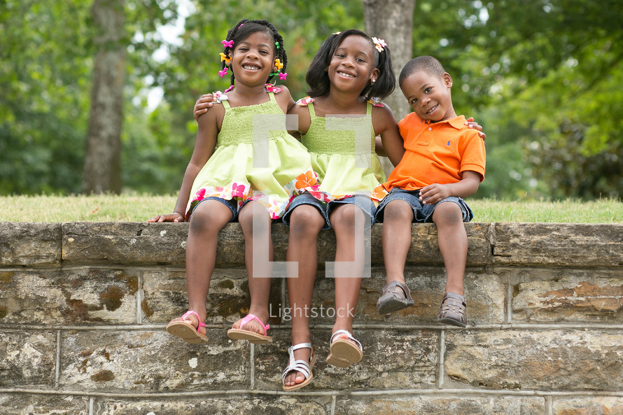 Happy sibling sitting on brick wall in the park