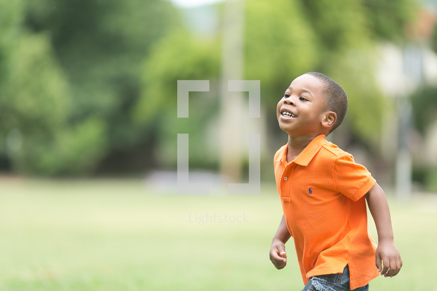 A smiling boy running