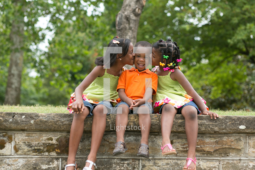 Sisters kissing their brother on the cheek