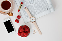 iPhone, red lipstick, Raspberries in a bowl, watch, magazine, rings, spoon, and coffee cup