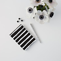 flowers in a black vase,  journal, and pens on a desk