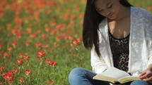 A girl sitting in a meadow of flowers reading a Bible outdoors