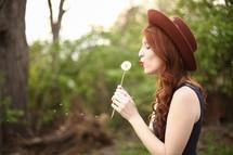 a woman blowing a dandelion