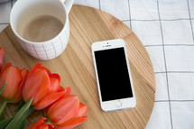 iPhone, tulips, and wood cutting board