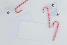 candy canes, bells, envelopes on white desk