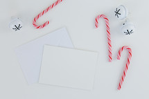 candy canes, bells, envelopes on white desk