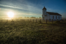 morning sun over a white rural church