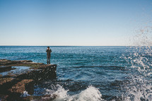 man standing on a rock by the ocean