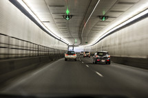 Cars driving through a long tunnel.