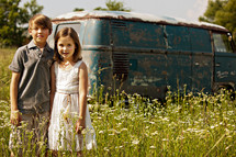 brother and sister in front of an old van in a field