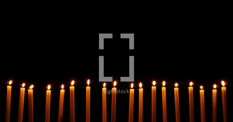 row of Christmas candles against black