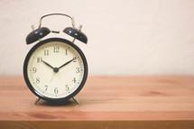 alarm clock on a wood shelf