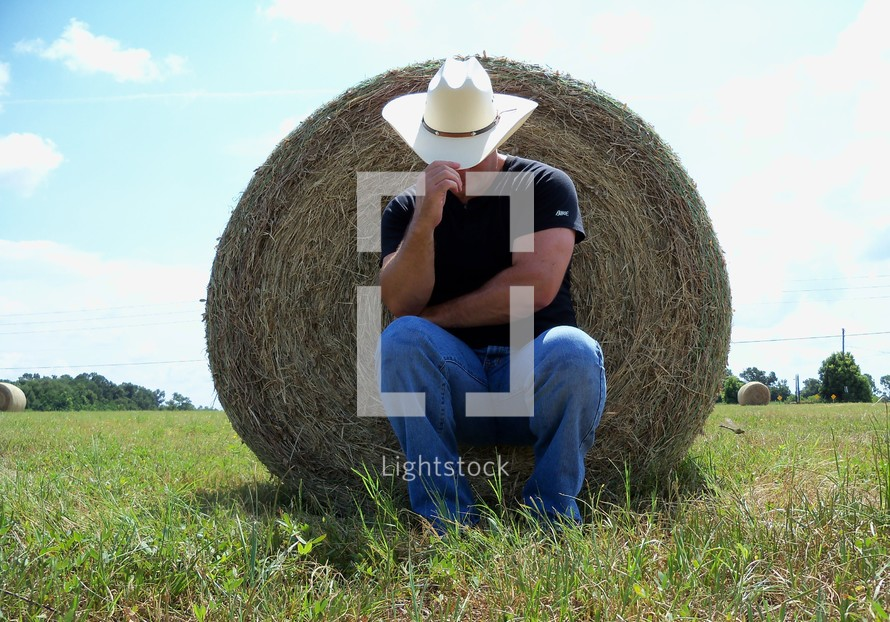 A cowboy with a cowboy hat tilts his hat to protect his face from the sun while resting in the shade behind a bale of hay in the country meadows of Florida.