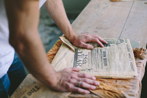Hands on a newspaper on a wooden table.