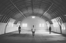 three men standing in an airplane hanger