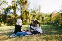 young women reading Bibles on a blanket outdoors
