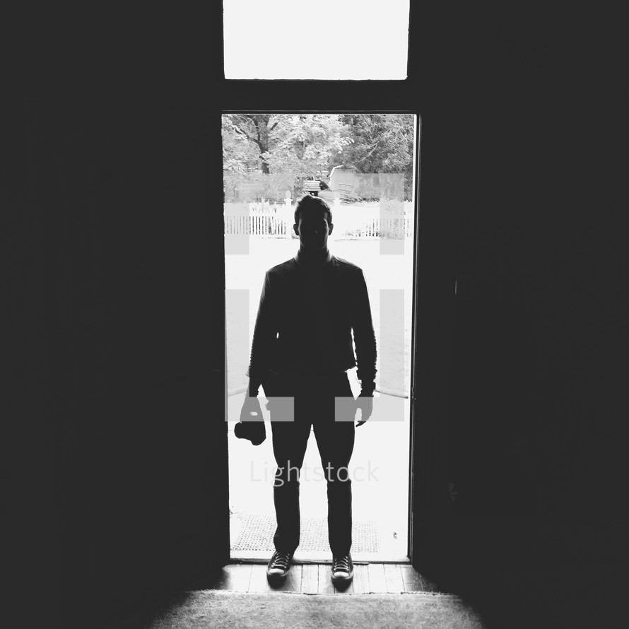 silhouette of a man standing in a doorway