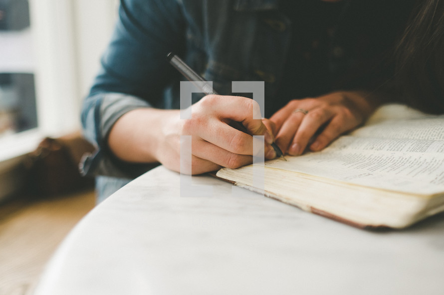 a woman taking notes on the pages of a Bible