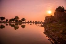 stone building along a river shore
