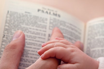 baby's hand holding Dad's finger over an open Bible
