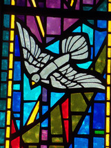 A stained glass window depicting the Holy Spirit descending like a dove surrounded by blue, red, lavender and gold colors adorning a church sanctuary worship center.