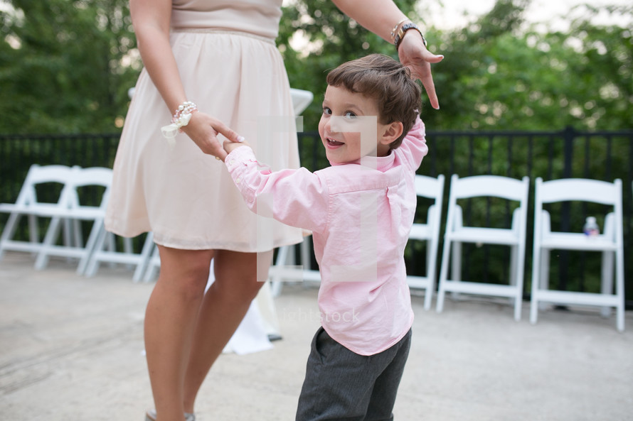 a young boy dancing with a woman at a wedding reception