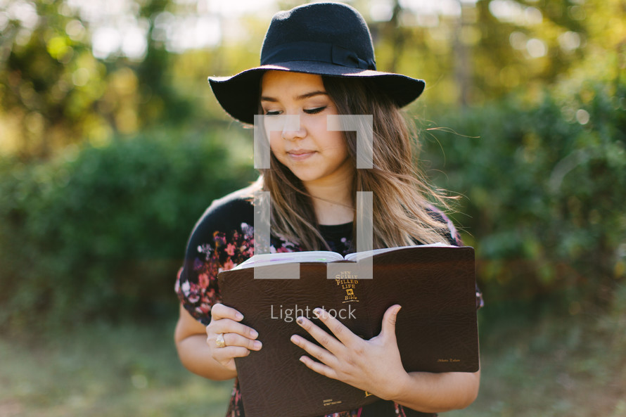 portrait of a teen girl in a hat standing outdoors reading a Bible