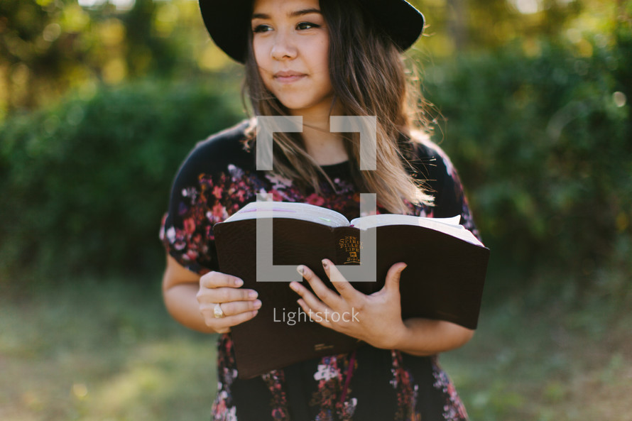 teen girl in a hat holding a Bible outdoors