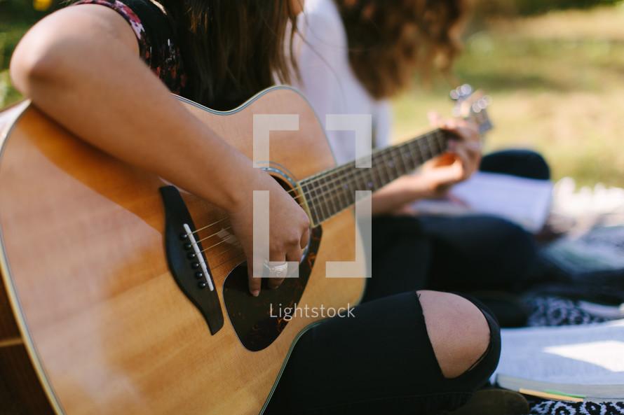 teen girl playing a guitar outdoors