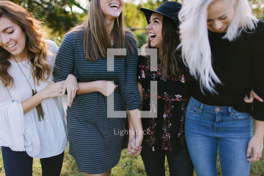 friends standing together outdoors laughing
