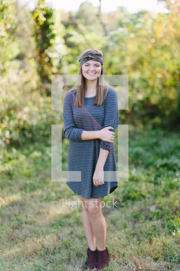 a teen girl standing outdoors