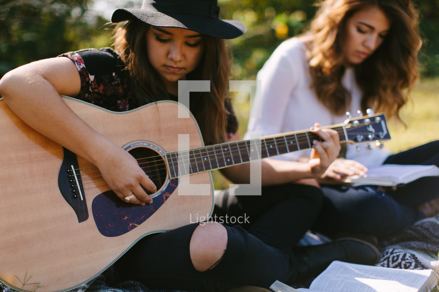 young women playing a guitar and singing