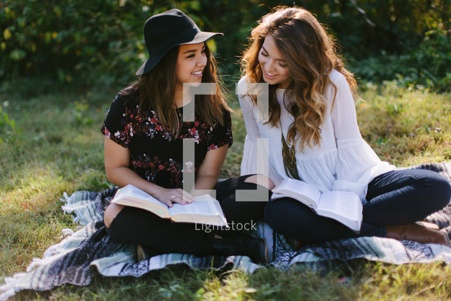 teen girls reading Bibles while sitting on a blanket outdoors