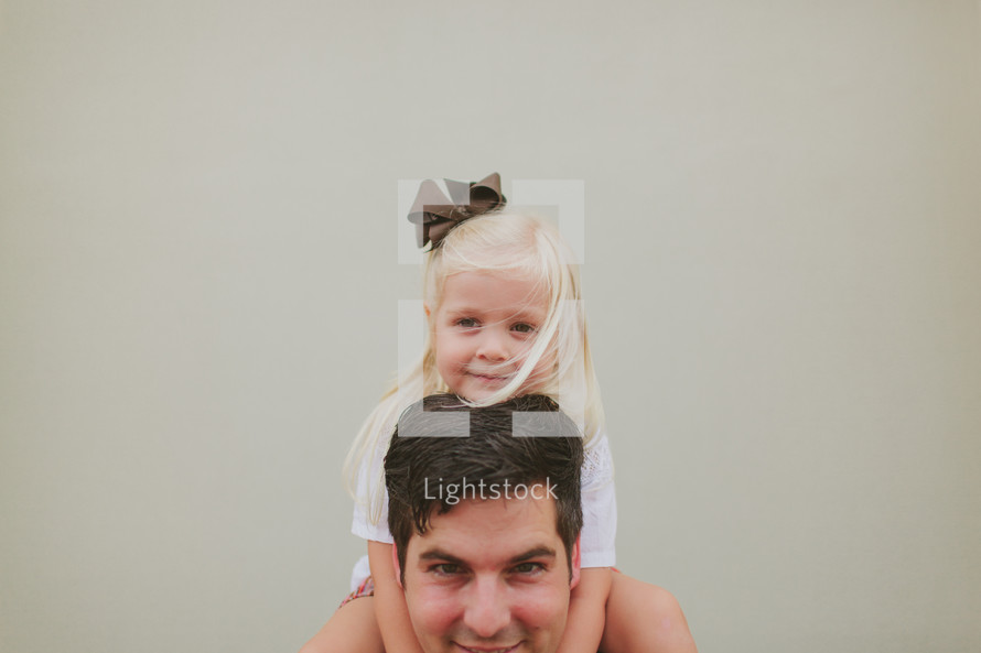 a daughter on her father's shoulders