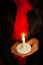 A woman holding a candle at a candlelight service