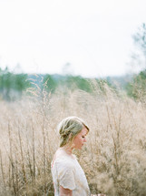 woman standing in a field of tall grasses and weeds