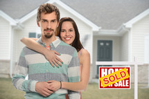 couple standing beside a sold sign in front of their new home