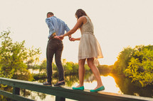 A couple holding hands and walking along the railing of a bridge