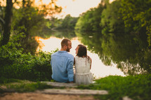 A happy couple relaxes by a river bed at dusk.