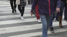 people crossing a crosswalk with shopping bags
