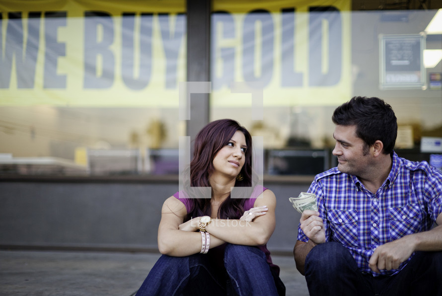man holding out cash to a woman in front of a we buy gold store