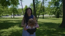 a mother pushing a toddler on a swing