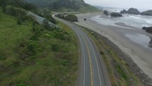 Aerial view of a car driving on a highway alongside the ocean shore.