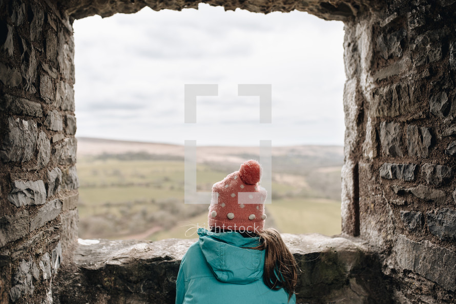 child looking out a castle window